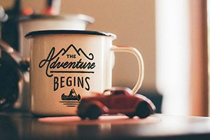 An enamel mug with a caption that says the adventure begins - signifying that change can be exciting