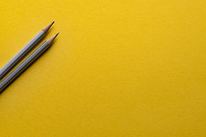 Two lead pencils on a yellow background, signifying strategic and corporate planning, business development and marketing strategy