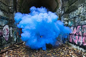 An explosion of blue powdered paint signifying the burst of ideas during innovation workshops and hackathons